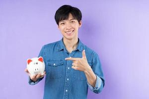 retrato, de, hombre asiático, en, camisa azul, posar, en, fondo púrpura foto