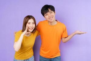 Retrato de pareja asiática, aislado sobre fondo púrpura foto