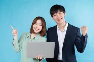 Playful business couple image isolated on blue background photo