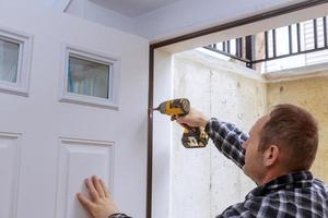 Carpintero proceso de instalación de la bisagra de la puerta manos atornillando la bisagra foto
