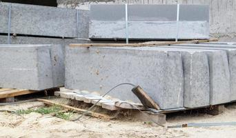 Faceted granite curbs on a pallet. Smooth porcelain stoneware products photo