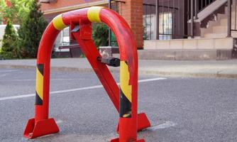 Manual red metal parking barrier with lock. Parking lock device. photo