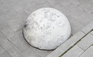 Round concrete road parking block in the shape of a hemisphere photo