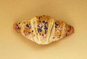 un croissant de grano entero crujiente fresco regular con chocolate. foto