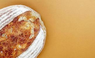 Freshly baked organic sourdough bread isolated on brown or coffee photo