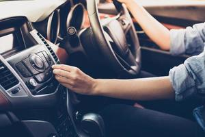 Las mujeres asiáticas presionan el botón de la radio del coche para escuchar música. foto