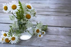 A bouquet of daisies in a glass jar. Floral background with place photo