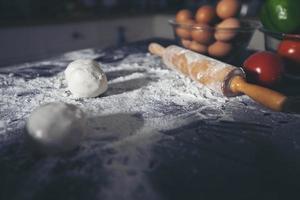 Preparing a pizza on kitchen table photo