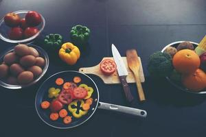 Food and fresh vegetables and salad bowls on kitchen table photo