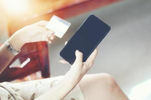 Woman using phone and credit card shopping online photo