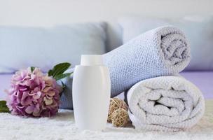 arreglo con toallas, botella y flor en la cama foto