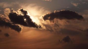 Fluffy clouds at sunset. Sun is shining behind the clouds at sky. video