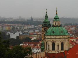 View of the city of Prague from the castle with the San Carlos bridge photo