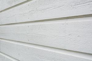 Close up of white wooden panel wall from side, shallow depth of field. photo