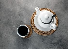 taza de té de porcelana blanca y tetera, mesa de té de la tarde foto