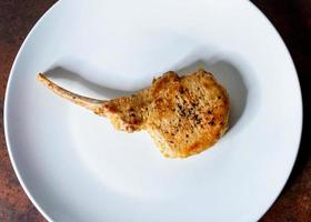 Roasted Pork Chop, Grilled pork loin served in a white dish photo