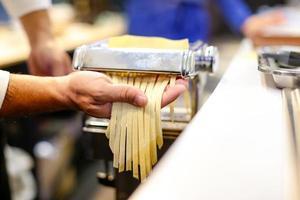 Chef making pasta with a machine, home made  fresh pasta photo