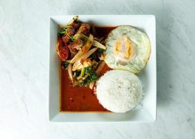 Salteado de cerdo crujiente frito y pasta de chile con arroz, comida tailandesa foto