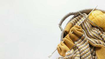 Agujas de tejer en una canasta de lana con espacio de copia foto