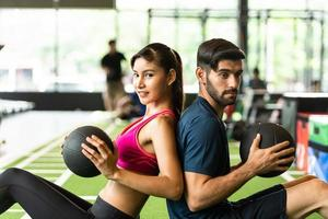 parejas jóvenes hacen ejercicio en el gimnasio para fortalecer el cuerpo. foto