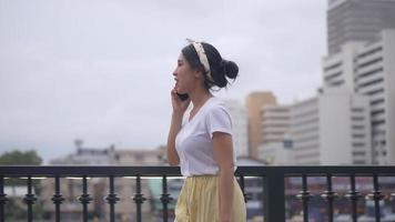 Beautiful young asian woman walking and  talking phone. video