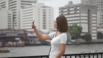 turista joven mujer asiática con video chat con teléfono inteligente.