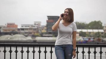 belle femme asiatique souriante parler au téléphone portable à côté de la rivière. video