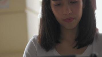 designer créatif de jeune femme asiatique à l'aide d'une tablette dans un café. video