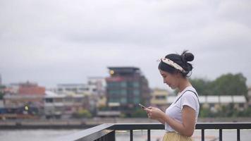 belle jeune femme asiatique à l'aide de smartphone. video