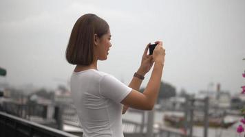 junge asiatische Frau mit Smartphone Foto machen. video