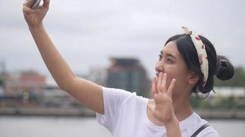 Beautiful young asian woman having video on social media.