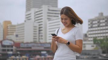 jeune femme asiatique utilisant un smartphone appréciant la lecture des médias sociaux. video