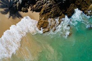 Vista aérea de arriba hacia abajo ola de la orilla del mar rompiendo en la orilla del mar foto