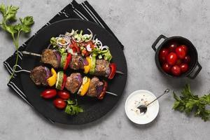 deliciosa comida rápida árabe, brochetas en placa negra y tomates foto