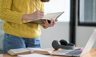 una estudiante toma notas en un cuaderno durante una clase en línea. foto