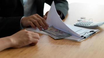 empresario escondiendo dinero en documentos para sobornar a funcionarios del gobierno. foto