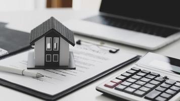 bolígrafo y casa modelo colocados en documentos contractuales con calculato. foto