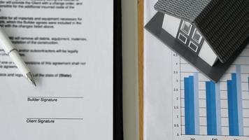bolígrafo colocado en documentos contractuales y casas modelo en gráficos de datos. foto