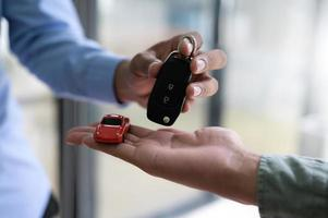 Close-up shot of exchanging car keys and model cars. photo