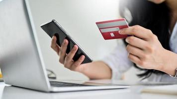 Young woman holding credit card and smartphone with laptop, photo