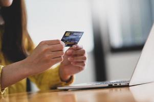 mujer joven con tarjeta de crédito en la mano y portátil sobre la mesa. foto