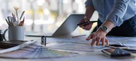 El diseñador gráfico tiene un teléfono inteligente con gráficos de colores. foto