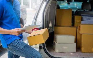 el mensajero lleva una caja de paquete y una tableta que verifica la dirección. foto