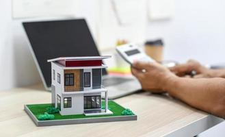 casa modelo con fondo borroso de una persona usando calculadora. foto