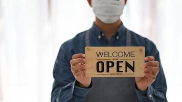 un joven con una máscara sostiene un cartel abierto para abrir el servicio. foto