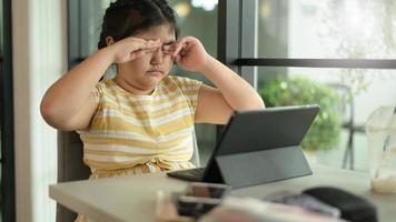 niña asiática cierra los ojos para descansar del uso de la tableta. foto