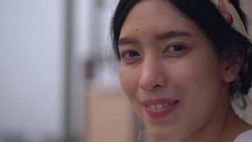 de cerca la cara sonriente joven mujer asiática mirando a la cámara. disparar a cámara lenta. video