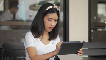 designer créatif de femme d'affaires asiatique utilisant une tablette dans un café pour planifier son projet. recherche sur Internet, technologie en ligne. tournage au ralenti. video