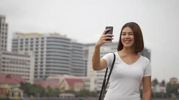 Beautiful young asian woman having video chat using smart phone connecting on social media summer vacation.