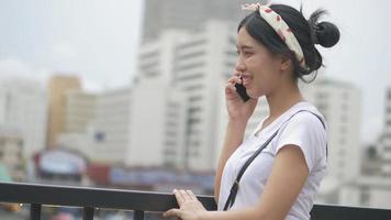 belle jeune femme asiatique parlant sur smartphone appréciant à côté de la clôture à la rivière. video